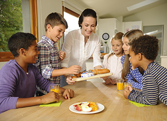 Woman & kids snacking on Bel cheese